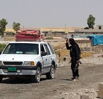 Image: A fighter with the Islamic State group directs a vehicle with a Christian family to leave from their home village outside Erbil