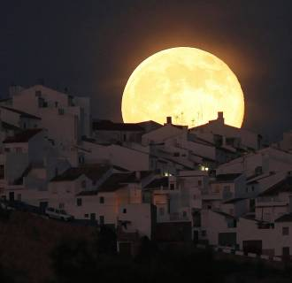 Image: The Supermoon rises over houses in Olvera