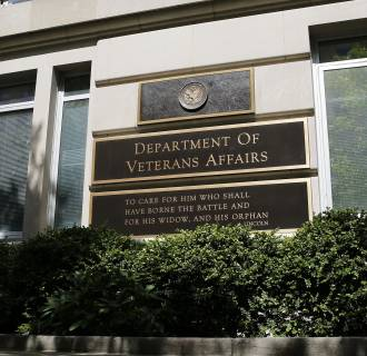 The sign in the front of the headquarters building at the Department of Veteran Affairs is seen as a woman walks past in Washington