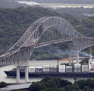 Image: A container ship sails underneath the Bridge of the Americas in the Panama Canal in Panama City