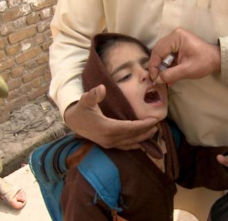 Image: A girl in Peshawar receives oral polio vaccine