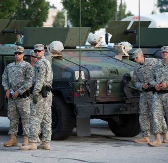 Image: National Guard troops arrive at a mall complex that serves as staging for the police in Ferguson