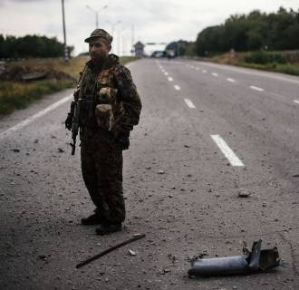 Image: A pro-Russia militant stands guard on a road near Donetsk