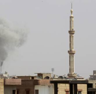 Image: Smoke rises after what activists said was an air raid by Syrian government forces at the eastern Syrian city of Raqqa