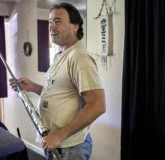iMAGE: Bill Long handles one of the guns, a .300-caliber magnum rifle, he keeps at his home in Nucla, Colo.