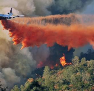 Image: An air tanker drops fire retardant on the Junction fire which was burning on a ridge northeast of Oakhurst, Calif.