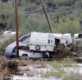Image: Damaged vehicles and trailers are seen in an area where flash flood waters that overran Skunk Creek