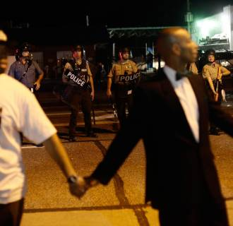 Image: Civilian peacekeepers join hands to separate demonstrators protesting against the shooting of Michael Brown away from the police in Ferguson