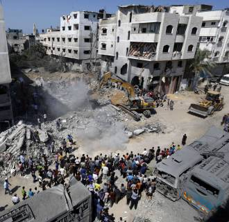 Image: A digger removes the cement and debris of a home destroyed the night before in an Israeli airstrike