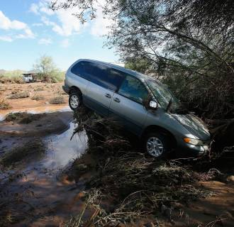 Image: A vehicle sits atop debris where flash flood waters pushed it after rising waters overran Skunk Creek