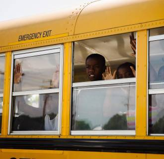 Image: Children on a school bus gesture and chant,