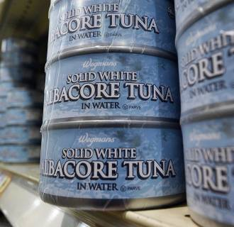 Canned tuna are pictured as a man shops