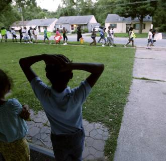 Image: Children watch from their home as people march about a mile to the police station to protest the shooting of Michael Brown on Aug. 20, in Ferguson, Mo