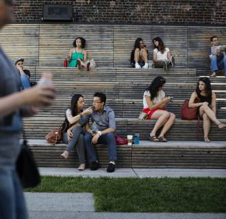 Pedestrians sit in a viewing area as pedestrians walk past on the High Line park in New York