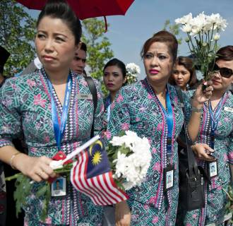 Image: Malaysia Airlines flight attendants hold white flowers during the arrival of the Malaysian remains who perished aboard flight MH17 that was downed in eastern Ukraine outside Bunga Raya complex in Sepang