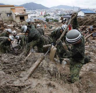Image: Japanese troops search for survivors on Friday in wake of landslide