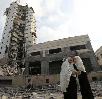 Image: Palestinian women stand next to the remains of one of Gaza's tallest apartment towers, which witnesses said was hit by an Israeli air strike that destroyed much of it, in Gaza City
