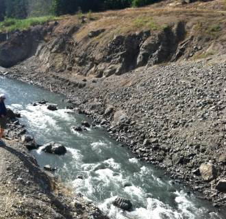 Image: Standing on a bluff at the former Elwha Dam site, a hiker overlooks rapids where the river now runs free.