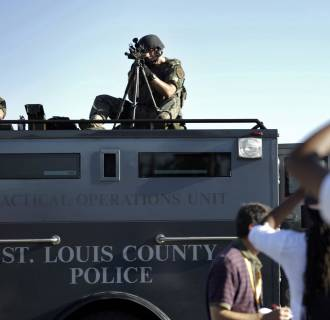 Image: A member of the St. Louis County Police Department points his weapon in the direction of a group of protesters in Ferguson, Mo.