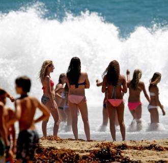 Image: Beachgoers watch large waves crash on the shore at Seal Beach, Calif.