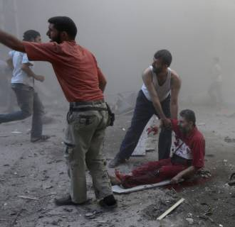 Image: Residents help an injured man at a site hit by what activists said were two airstrikes by forces loyal to Syria's President Bashar al-Assad in Douma in eastern al-Ghouta