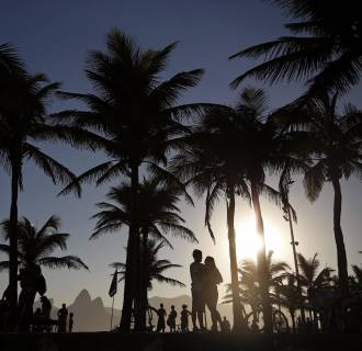 Image: A couple embrace as they wait to view the sunset at Arpoador Beach in Rio de Janeiro on Aug. 24, 2014.