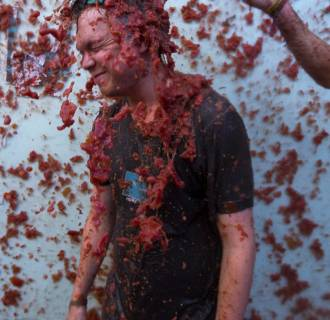 Image: A young man is showered with tomatoes as he takes part in the traditional La Tomatina Festival