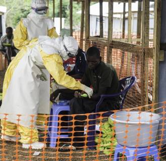 Image: A medical team at the Doctors Without Borders Ebola treatment center in Kailahun, Sierra Leone perform rounds in the center's high-risk area