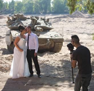 Image: Israeli couple, Noga and Moshiko Siho, have their wedding photo taken in an army staging area on the Israeli Gaza border, near Kibbutz Yad Mordechai, Israel