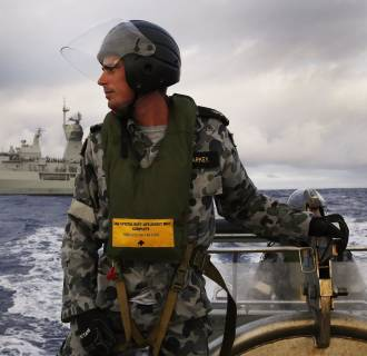 Image: Leading Seaman, Boatswain's Mate, William Sharkey searching for debris on a rigid hull inflatable boat as HMAS Perth searches for missing Malaysia Airlines flight MH 370