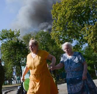 Image: Women rush across the street after shelling in the town of Donetsk, eastern Ukraine