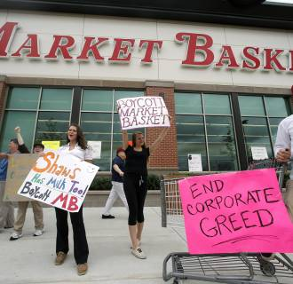 Image: Market Basket employees Rees Gemmell, far right, and colleagues acknowledge passing supporters as they picket in front of the store