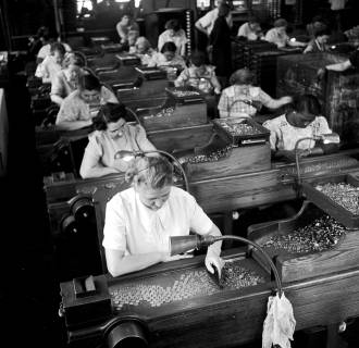 Image: Quality control inspectors in a mint in Philadelphia look out for blemished coin in 1948.