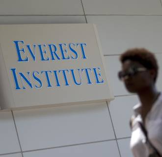 Image: A person walks past an Everest Institute sign in a office building in Silver Spring, Md., on July 8.