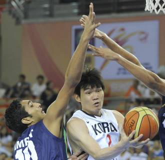 Image: Kim Joo Sung of South Korea, center, tries to pass the ball as Amjyot Singh, right, and Amritpal Singh of India defend during their preliminary round match between South Korea and India at the 26th Asian Basketball Championships in Wuhan in China