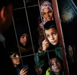 Syrian children wait as Bulgarian doctors perform medical checkups at a refugee centre in Sofia