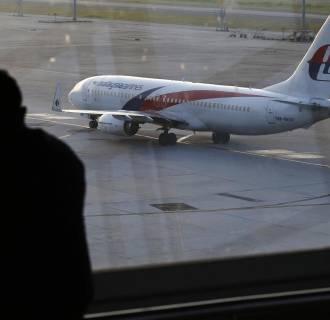 Image: A man watches a Malaysia Airlines jet at Kuala Lumpur International Airport