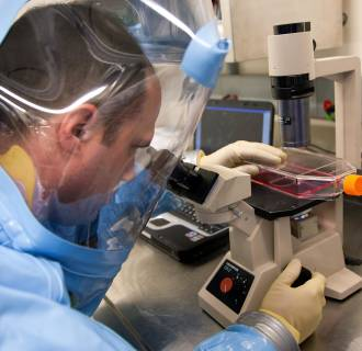Image: Employees of the Public Health Agency of Canada working inside of the National Microbiology Laboratory's Level 4 lab.