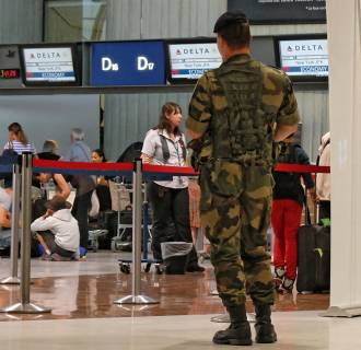 Image: A French soldier stands in front of the desk of the Delta Airlines desk in Nice airport