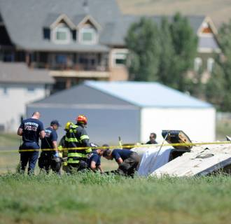 Image: Police and firefighters work on the scene where three people were killed and two others injured after an airplane crashed while coming in for a landing in Erie, Colo.