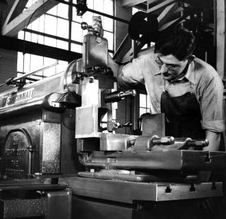 Image: A factory worker makes parts using a machine circa 1940.