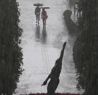 Image: Tennis fans exit the Billie Jean King National Tennis Center as a heavy rain falls