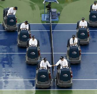 Image: Workers dry the court after a suspension of play due to rain at the 2014 U.S. Open tennis tournament in New York