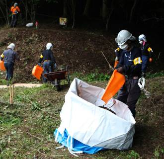 Image: Decontamination workers remove radiated soil and leaves from a forest in Kawauchi village, Fukushima prefecture