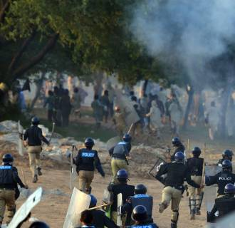 Image: Pakistani riot police run towards supporters of cricketer-turned-politician Imran Khan and Canadian cleric Tahir ul Qadri during clashes
