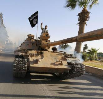 Image: Militant Islamist fighters on a tank take part in a military parade along the streets of northern Raqqa province