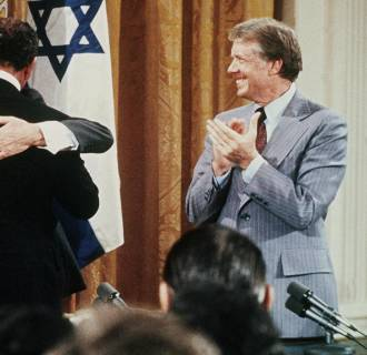 Image: Egyptian President Anwar al-Sadat and Israeli Premier Menachem Begin hug as U.S. President Jimmy Carter looks on