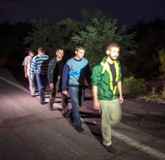 Image: Ukrainian government forces, who are prisoners-of-war, walk along a road as they wait to be exchanged, north of Donetsk, eastern Ukraine