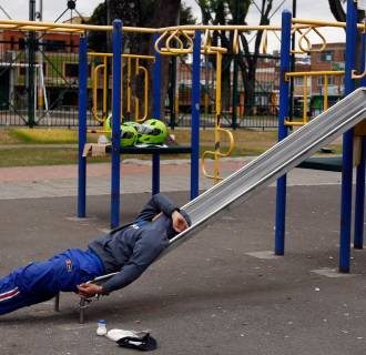 A detainee rests, handcuffed to a slide, at a children's playground in a public park in Bogota, Colombia, Thursday, Sept. 11, 2014. Due to overcrowding at a detention center located across the street, the park has been converted into makeshift holding are