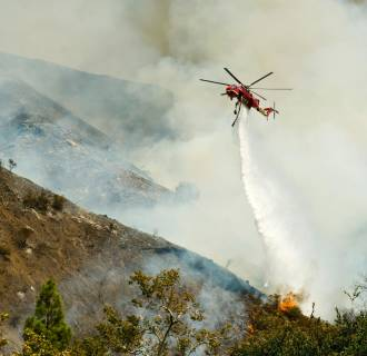 Image: An Orange County Fire Authority helicopter drops a load of water on a brush fire in Silverado Canyon in Orange County, Calif.